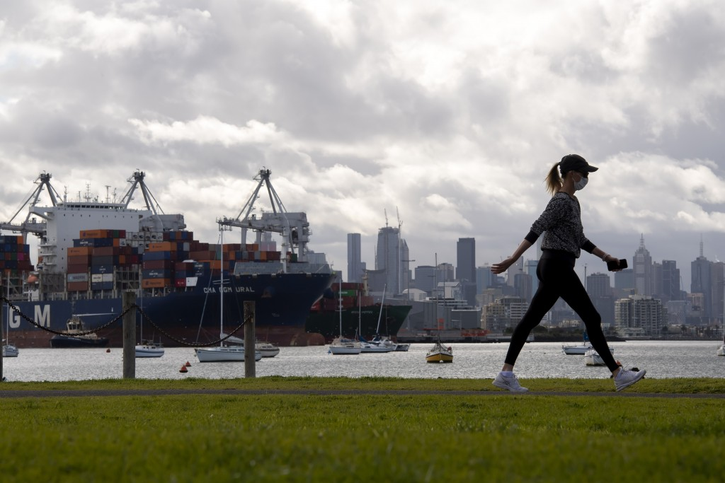 A woman takes a walk in a park during lockdown due to the continuing spread of the coronavirus in Melbourne, Thursday, Aug. 6, 2020. Victoria state, A...