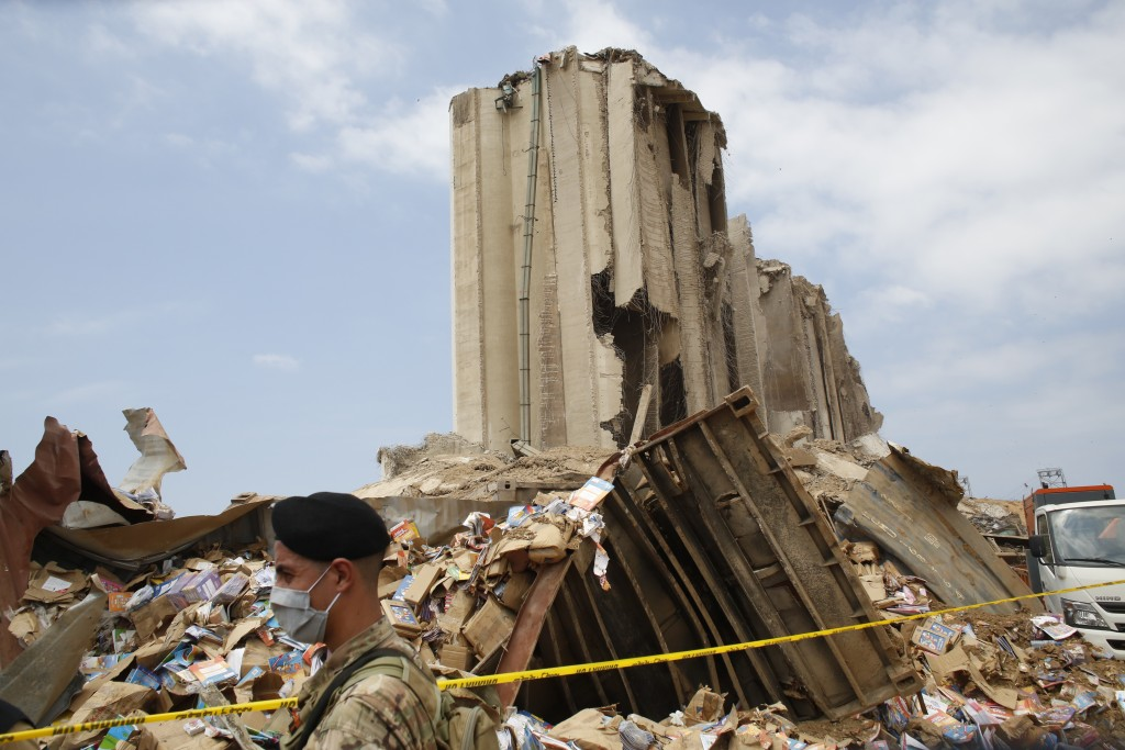 A soldiers walks past rubbles at the devastated site of the explosion at the port of Beirut, Lebanon, Thursday Aug.6, 2020. French President Emmanuel ...