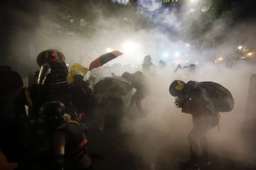 FILE - In this July 26, 2020, file photo, federal officers launch tear gas at demonstrators during a Black Lives Matter protest at the Mark O. Hatfiel...