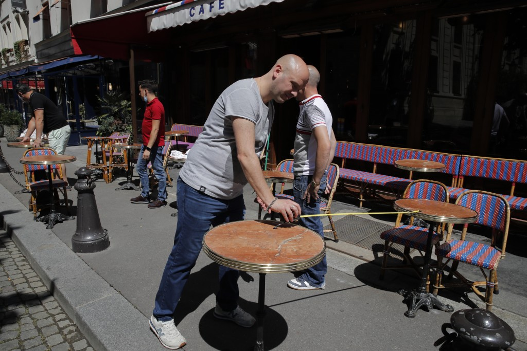 Waiters prepare the terrace of a restaurant in order to respect distancing measures in Paris, Monday, June 1, 2020, as France gradually lifts its Covi...