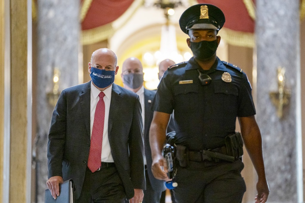 Postmaster General Louis DeJoy, left, is escorted to House Speaker Nancy Pelosi's office on Capitol Hill in Washington, Wednesday, Aug. 5, 2020.  Faci...