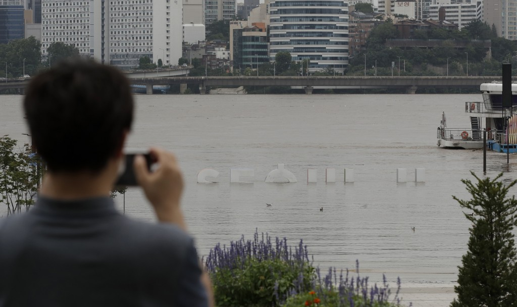 The display of South Korea's capital Seoul logo is partially submerged due to heavy rain at a park near the Han River in Seoul, South Korea, Thursday,...