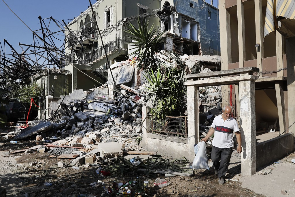 A Lebanese man carries his belongings as he leaves his destroyed house near the scene where an explosion hit on Tuesday the seaport of Beirut, Lebanon...