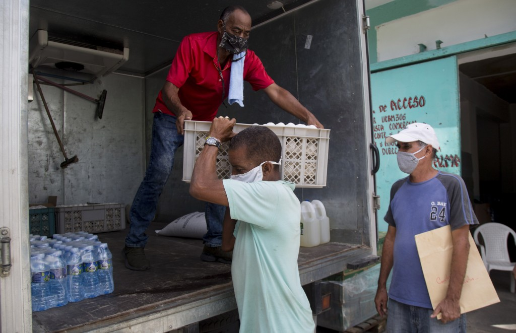 Cafeteria owner Miguel Sanchez, right, inspects his purchase as a porter loads his items into a courier service's truck, to take to his restaurant fro...