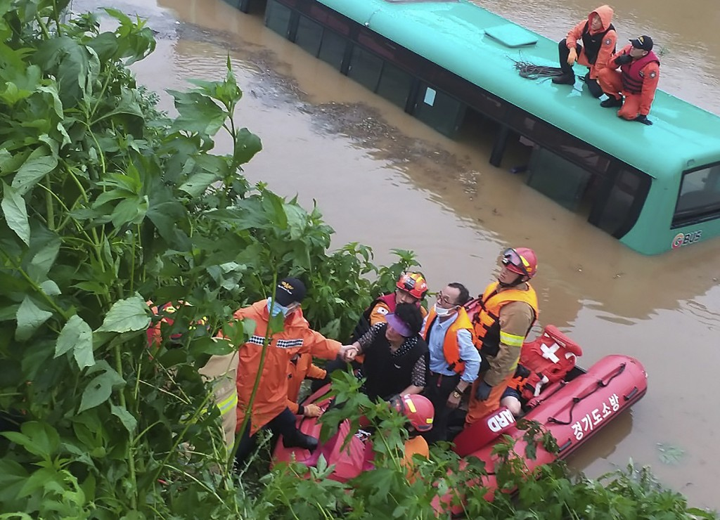 Rescue workers evacuate passengers on a boat from a submerged bus due to heavy rain in Paju, South Korea, Thursday, Aug. 6, 2020. Korean Meteorologica...