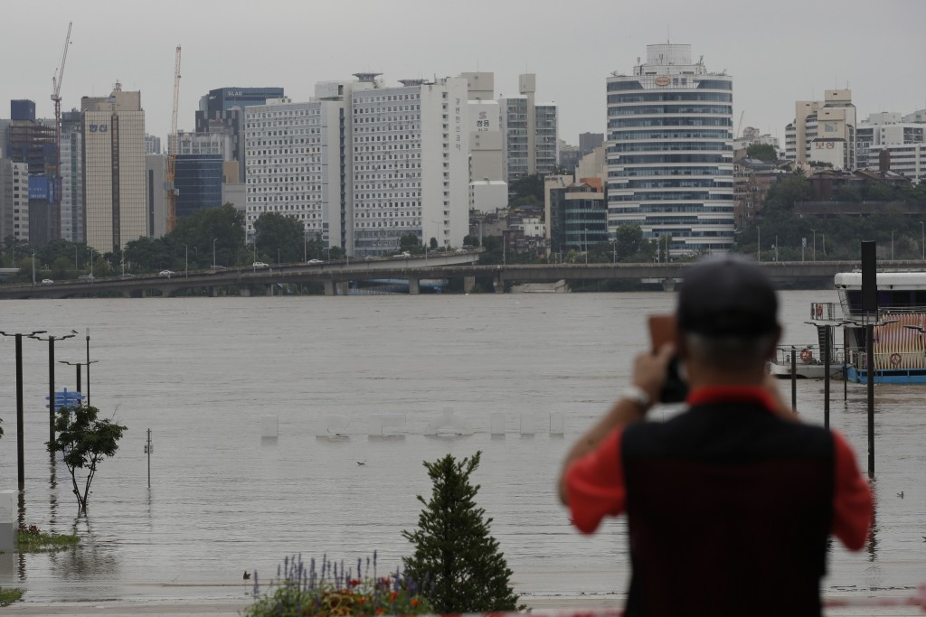The display of South Korea's capital Seoul logo is almost submerged due to heavy rain at a park near the Han River in Seoul, South Korea, Thursday, Au...