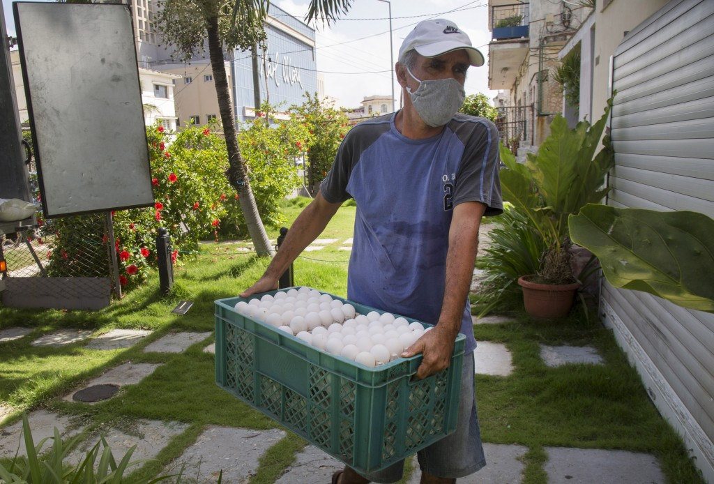 Cafeteria owner Miguel Sanchez unloads his purchase of eggs, bought at the Mercabal wholesale market, as he arrives home in Havana, Cuba, Friday, July...