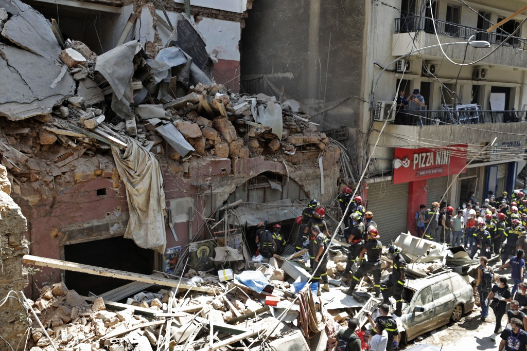 French and Lebanese firemen search in the rubble of a building after the Tuesday explosion at the seaport of Beirut, in Beirut, Lebanon, Thursday, Aug...