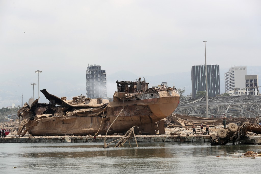 People stand by the wreckage of a ship at the devastated site of the explosion in the port of Beirut, Lebanon, Thursday Aug.6, 2020. French President ...