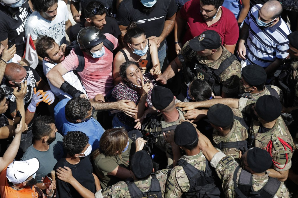 A woman yells at Lebanese soldiers during scuffles with the soldiers who are blocking a road as French President Emmanuel Macron visits the Gemmayzeh ...