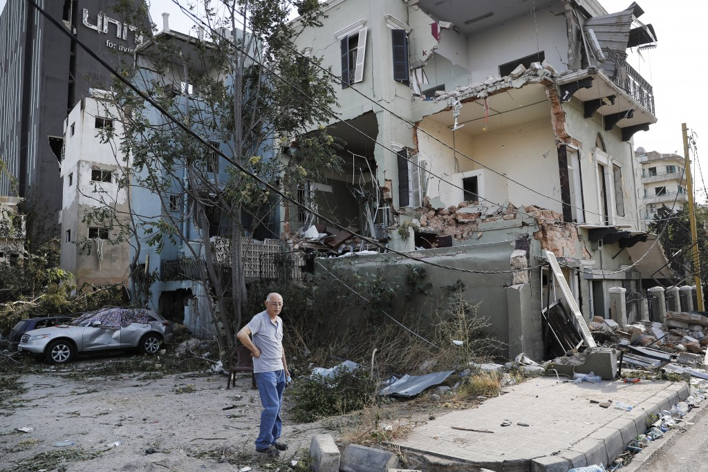 A Lebanese man stands next to his damaged house near the scene where an explosion hit on Tuesday the seaport of Beirut, Lebanon, Thursday, Aug. 6, 202...