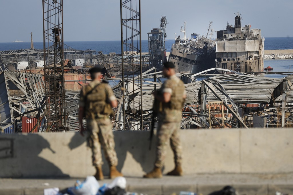 Lebanese army soldiers stand guard in front of destroyed ships at the scene where an explosion hit on Tuesday the seaport of Beirut, Lebanon, Thursday...