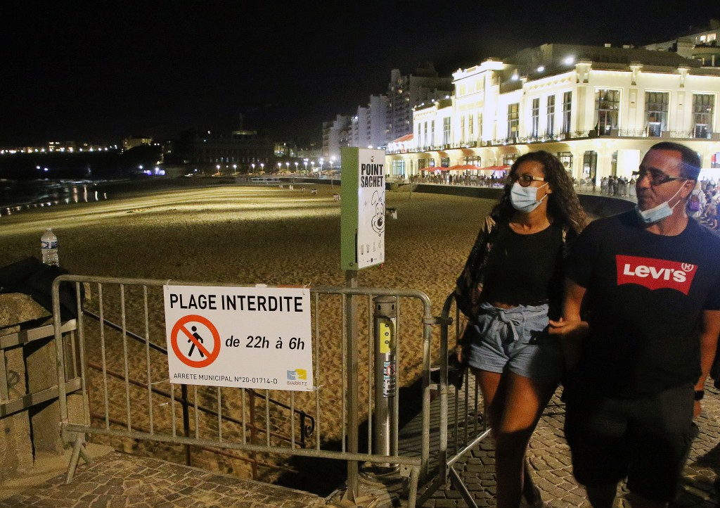 People wear face masks as they walk near the closed beach in Biarritz, southwestern France, Wednesday, Aug. 5, 2020. Biarritz beach is closed all nigh...