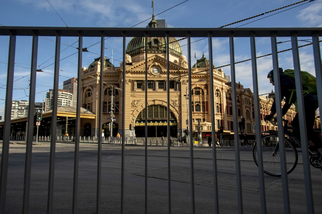 A cyclists passes an empty Flinders Street Station during lockdown due to the continuing spread of the coronavirus in Melbourne, Thursday, Aug. 6, 202...
