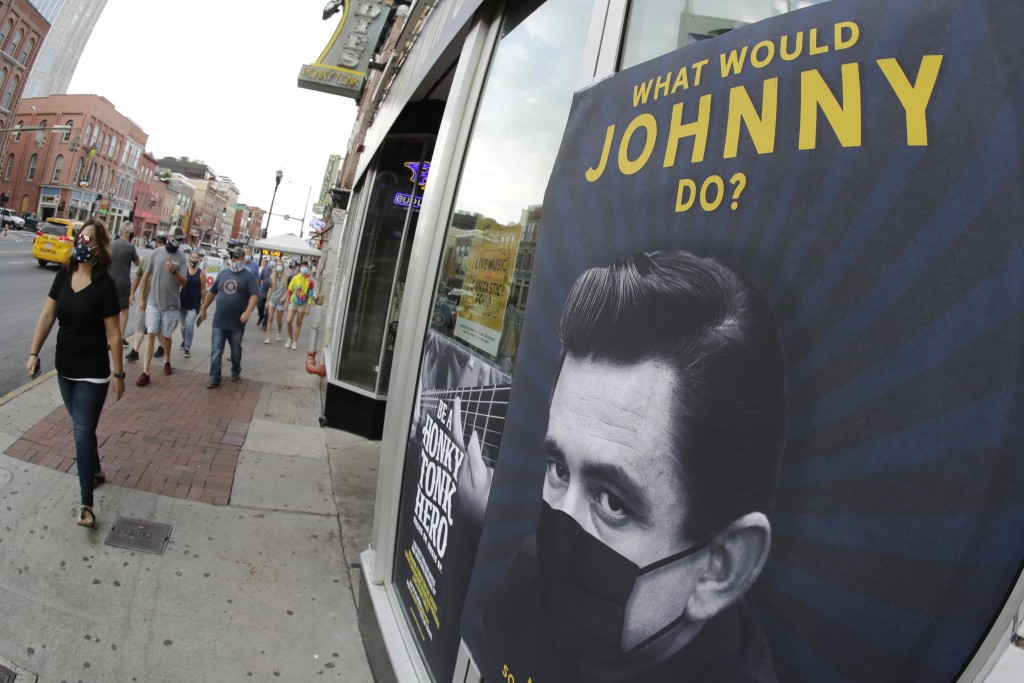 A poster showing country music legend Johnny Cash wearing a mask is attached to a storefront Wednesday, Aug. 5, 2020, in Nashville, Tenn. The wearing ...