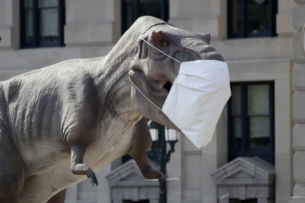 A dinosaur replica wears a mask outside Union Station in Kansas City, Mo., Wednesday, Aug. 5, 2020. The dinosaur is promoting a Dinosaur Road Trip exh...