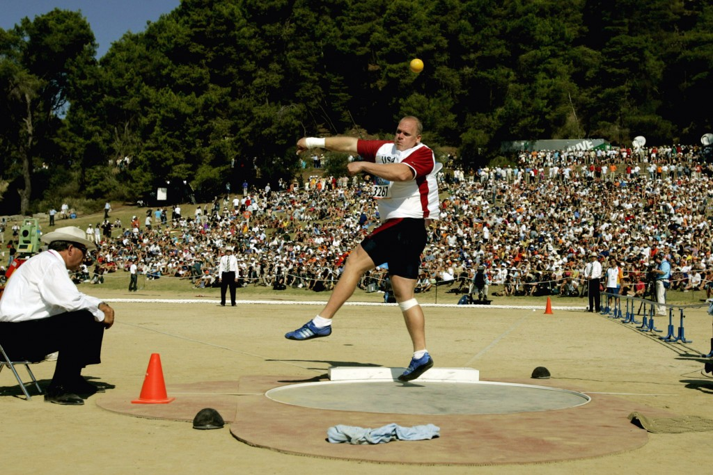 FILE - In this Aug. 18, 2004, file photo, John Godina, of the United States, makes a qualifying throw during the Athens 2004 Olympics men's shot put q...