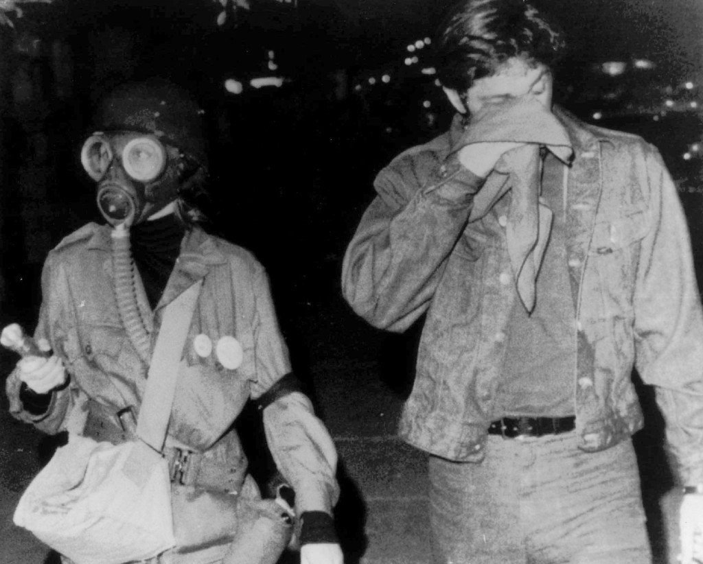 FILE - In this Aug. 27, 1968, file photo, a woman wears a gas mask as she walks with a companion holding a cloth to his eyes after they were sprayed w...