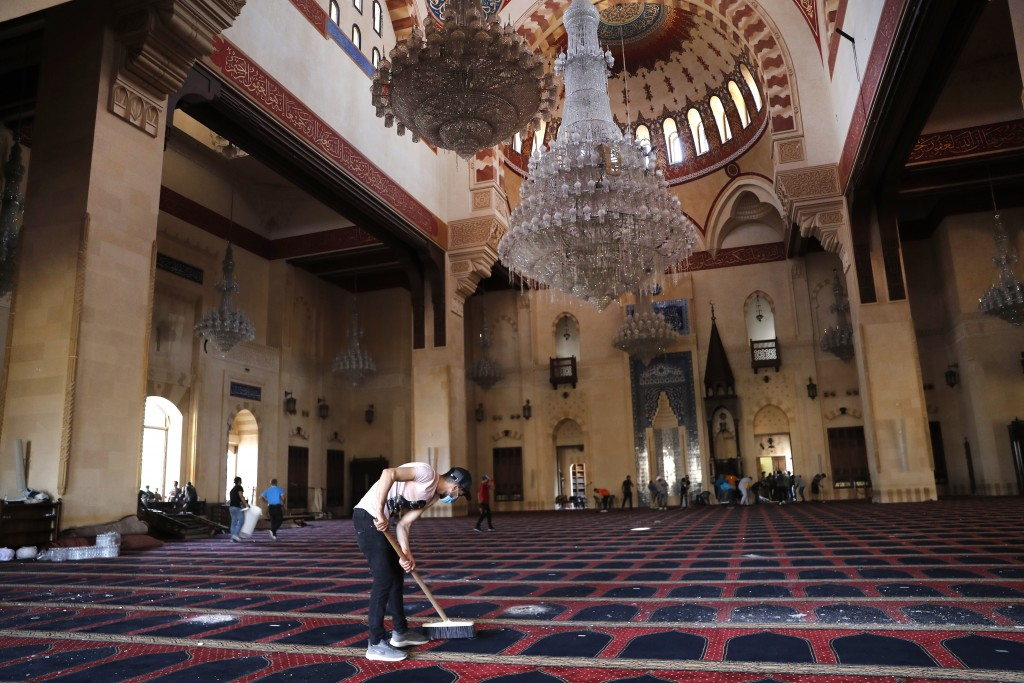 A man cleans a damaged mosque a day after an explosion hit the seaport of Beirut, Lebanon, Wednesday, Aug. 5, 2020. (AP Photo/Hussein Malla)