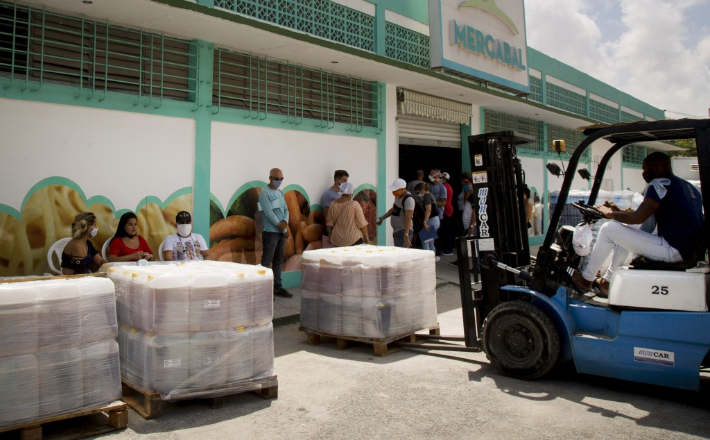 A worker moves goods with a forklift at the entrance of Mercabal wholesale market where customers wait to enter in Havana, Cuba, Thursday, July 30, 20...