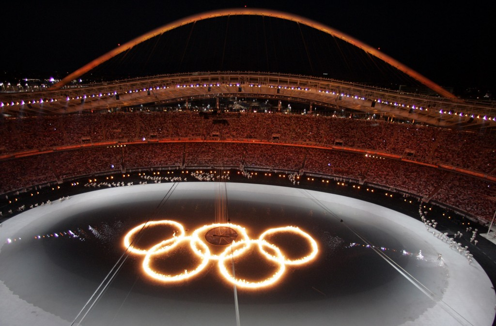 FILE - In this Aug. 13, 2004, file photo, the Olympic Rings are shown in flames in a pool of water during the Opening Ceremony of the 2004 Olympic Gam...