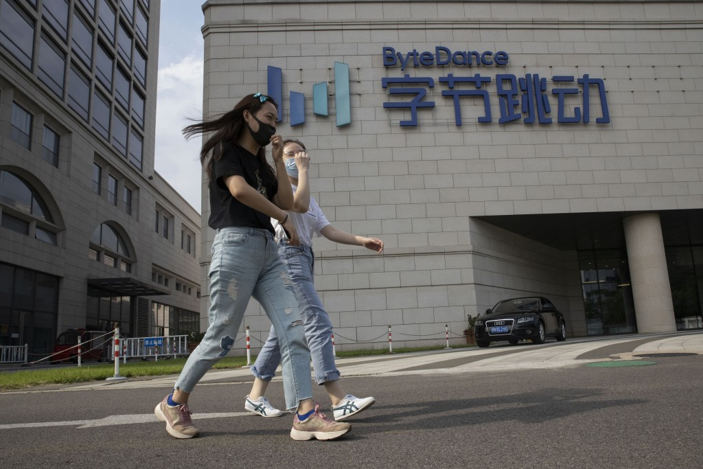Women wearing masks to prevent the spread of the coronavirus chat as they pass by the ByteDance headquarters in Beijing, China on Friday, Aug. 7, 2020...