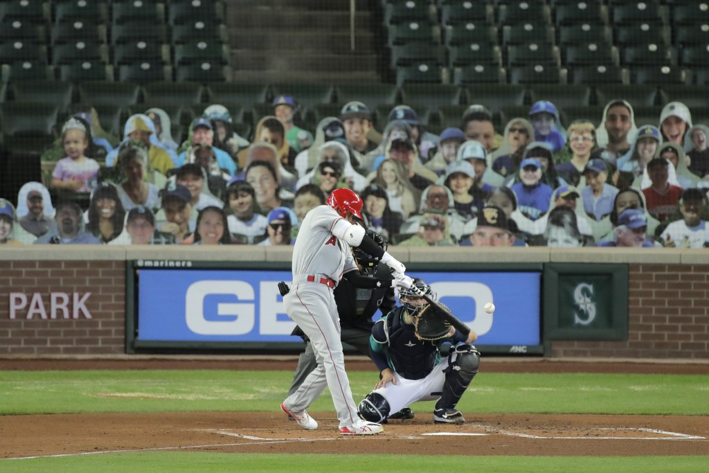 Los Angeles Angels' Shohei Ohtani hits a solo home run as Seattle Mariners catcher Joe Hudson looks on during the second inning of a baseball game, Th...