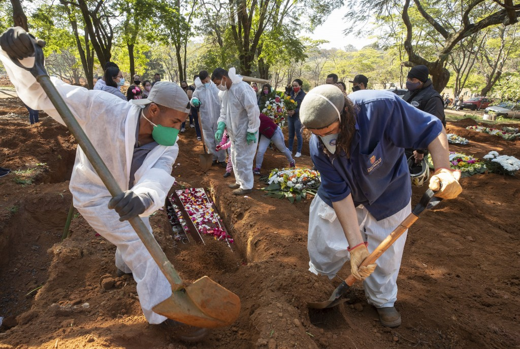 Cemetery workers bury 65-year-old Maria Joana Nascimento, whose family members, behind, suspect died of COVID-19, at Vila Formosa cemetery in Sao Paul...