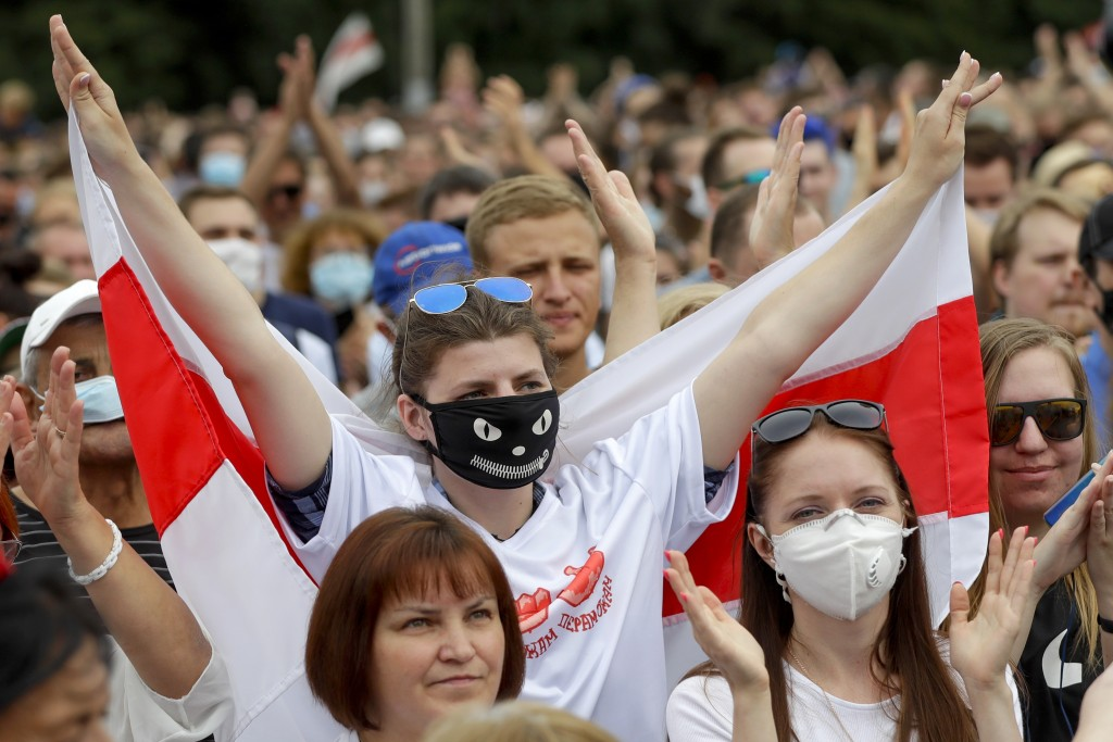 FILE - In this file photo taken on Sunday, July 19, 2020, Belarusians, some of them wearing face masks to protect against coronavirus, attend a meetin...