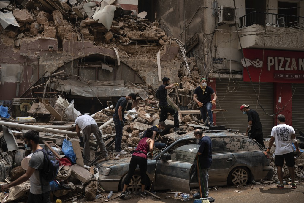 People remove debris from a house damaged by Tuesday's explosion in the seaport of Beirut, Lebanon, Friday, Aug. 7, 2020.  Rescue teams were still sea...