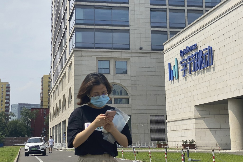 A woman uses her phone as she passes by the ByteDance headquarters in Beijing, China, on Friday, Aug. 7, 2020. President Donald Trump on Thursday orde...