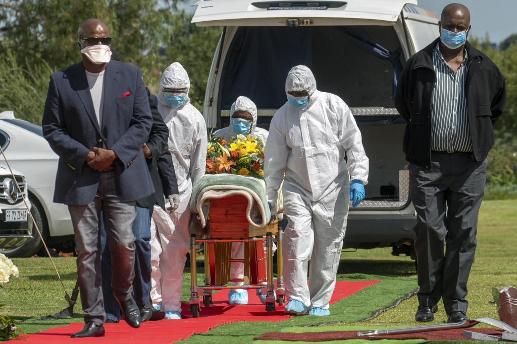 FILE - In this April 16, 2020, file photo, pallbearers wearing personal protective equipment suits lift the casket containing the remains of Benedict ...