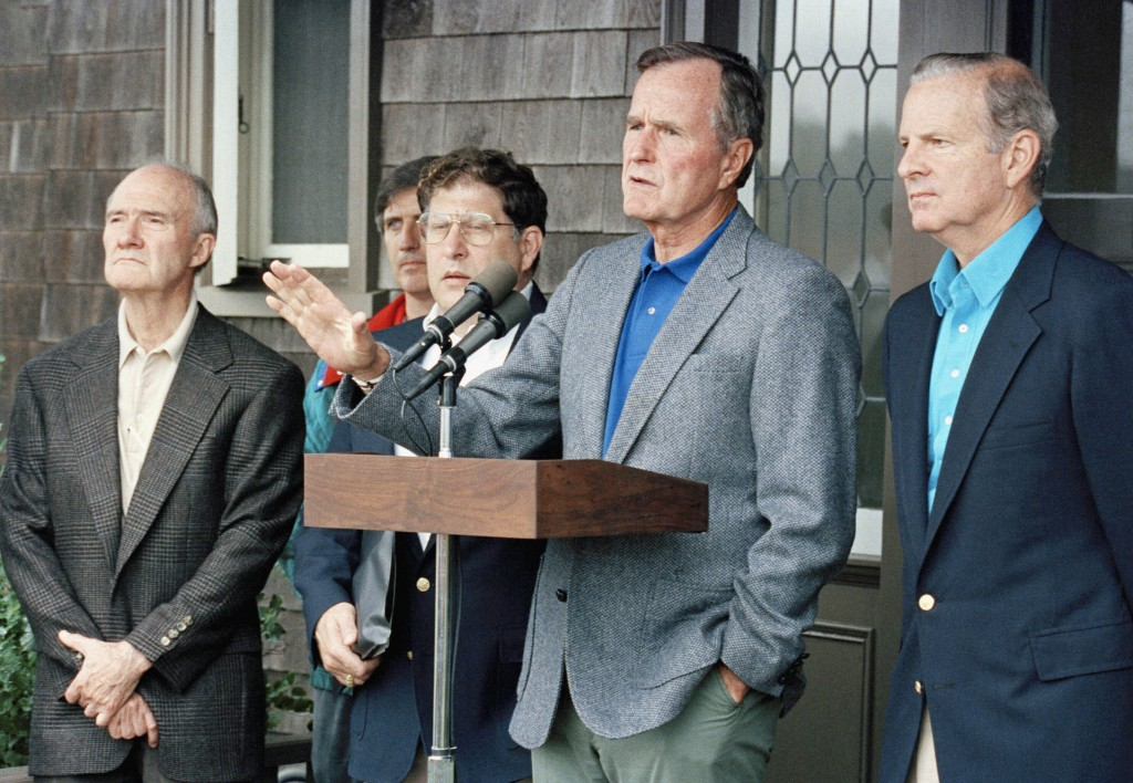 FILE - In this August 11, 1990 file photo, President George H. W. Bush comments to reporters at his Kennebunkport home in Maine, after meeting with hi...