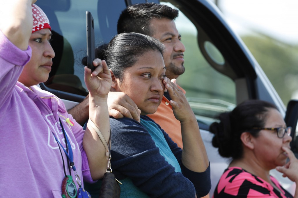 FILE - In this Aug. 7, 2019, file photo, Friends, coworkers and family watch as U.S. immigration officials raid the Koch Foods Inc., poultry processin...