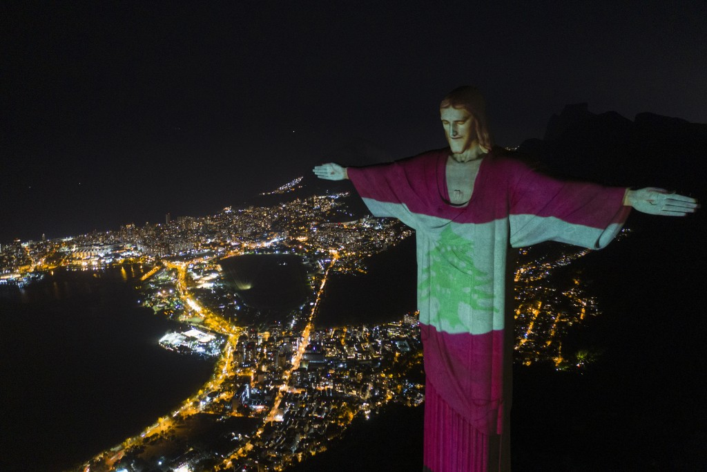 The Christ the Redeemer statue is lit up with an image depicting the Lebanon national flag in Rio de Janeiro, Brazil, Thursday, Aug. 6, 2020, in solid...