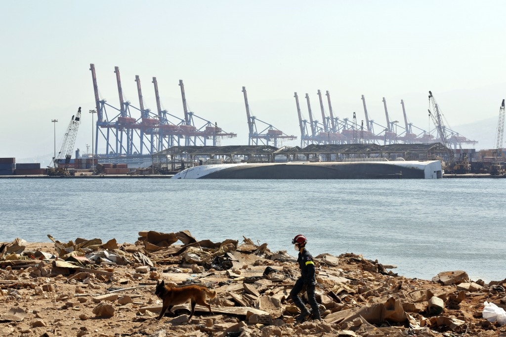 A French rescue team worker walks with his dog as they search for survivors at the scene of this week's massive explosion in the port of Beirut, Leban...