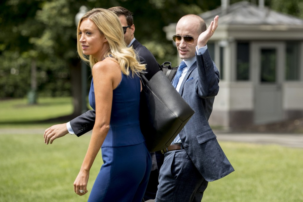 White House Press Secretary Kayleigh McEnany, left, and President Donald Trump's White House senior adviser Stephen Miller, right, walk across the Sou...