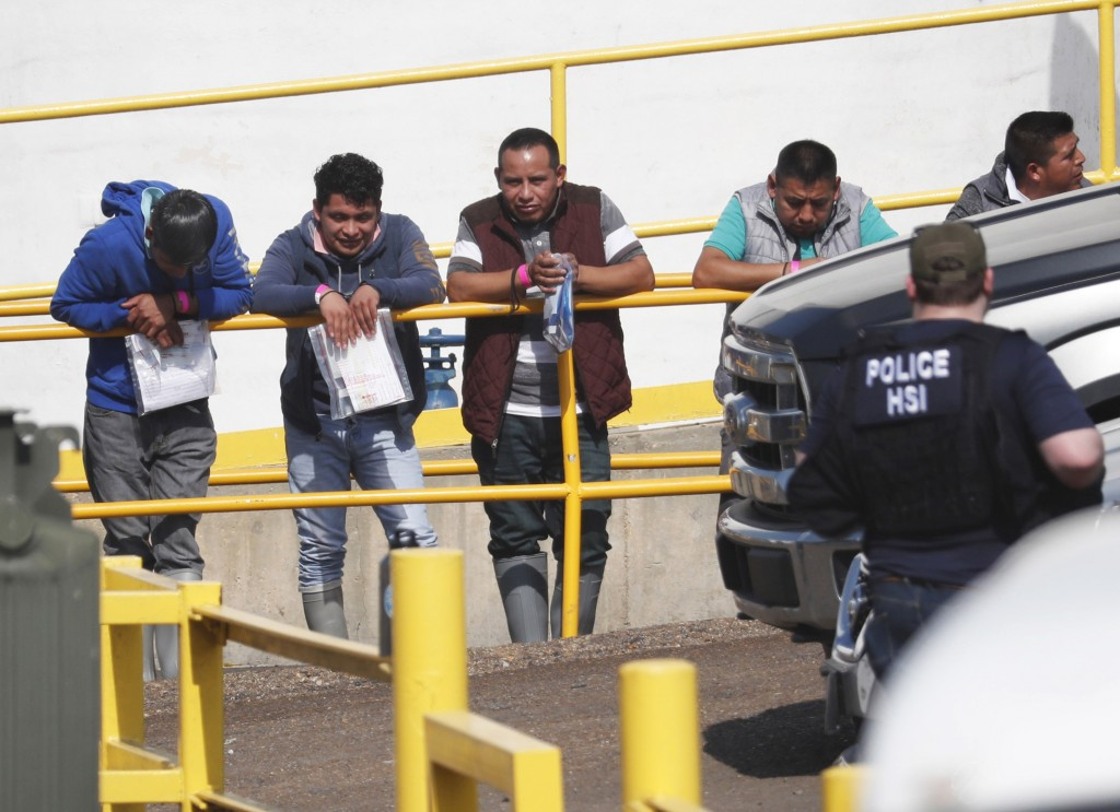 FILE - In this this Aug. 7, 2019, file photo, handcuffed workers await transportation to a processing center following a raid by U.S. immigration offi...