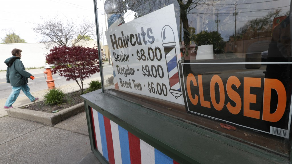 FILE - In this May 6, 2020 file photo, a woman walks past a closed barber shop in Cleveland. Small businesses are in limbo again as the coronavirus ou...