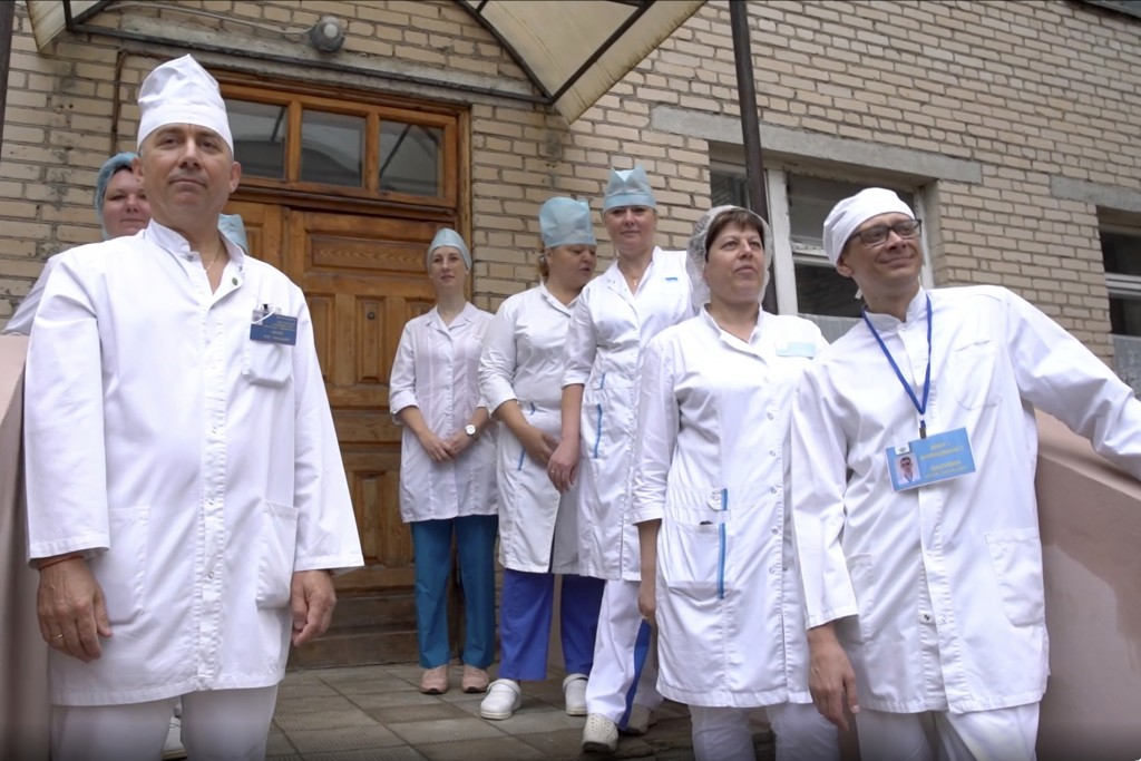In this photo made from footage provided by the Russian Defense Ministry on Wednesday, July 15, 2020, medical workers look at volunteers participating...