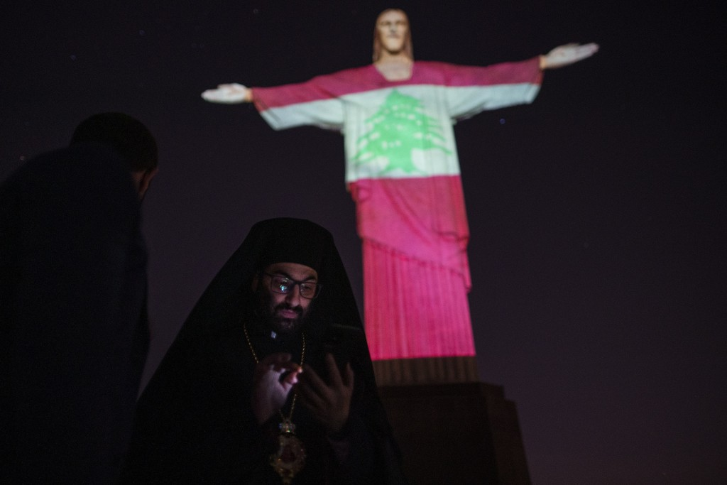 Bishop Theodore Ghandour of the Orthodox Church of Antioch attends a ceremony where the Christ the Redeemer statue is lit up with an image depicting t...