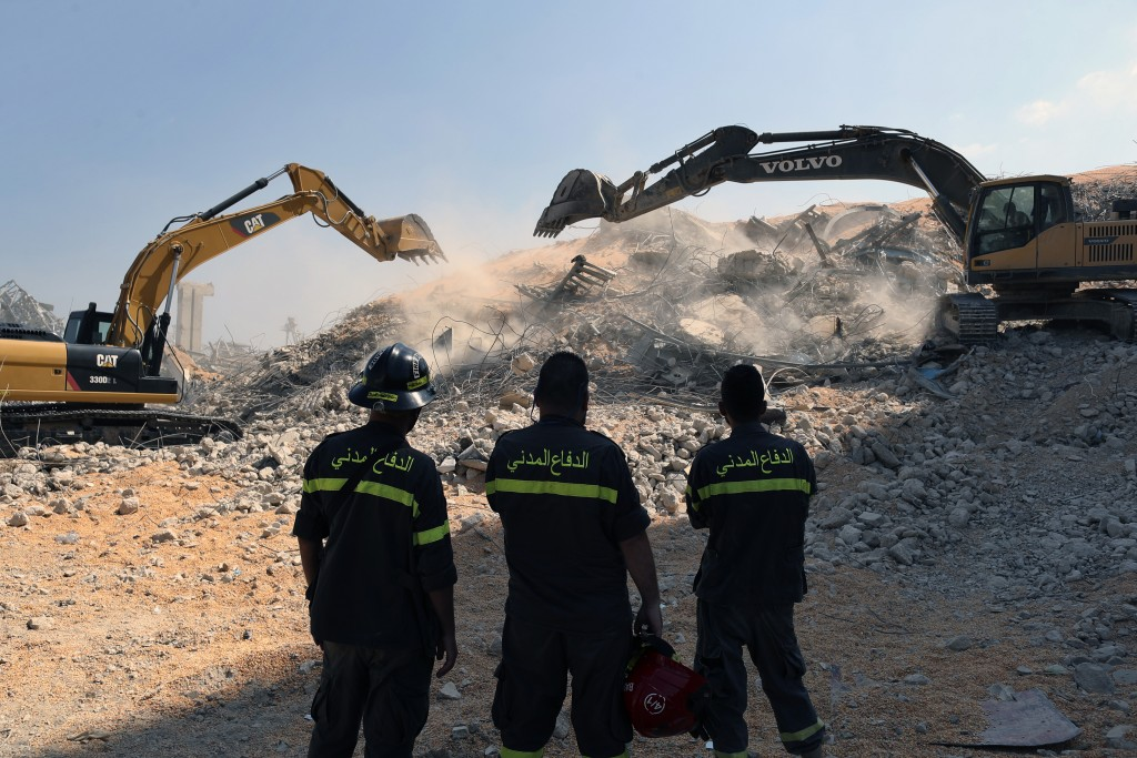 A rescue team watch diggers tackle the removal of debris from this week's massive explosion in the port of Beirut, Lebanon, Friday, Aug. 7, 2020. Thre...