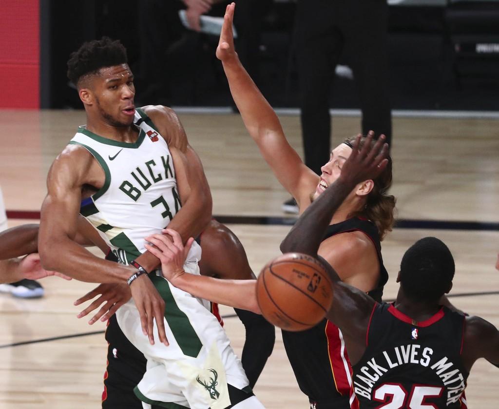 Milwaukee Bucks forward Giannis Antetokounmpo (34) passes the ball against Miami Heat forward Kelly Olynyk (9) and guard Kendrick Nunn (25) during the...