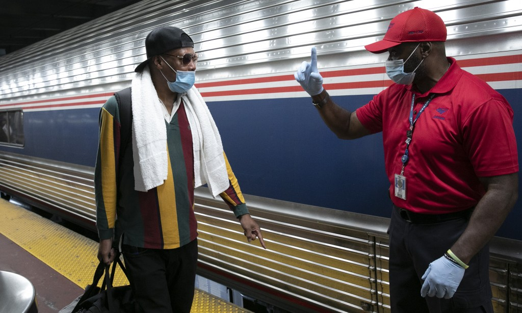A traveler arriving on a train that originated in Miami gets directions from a porter, right, at Amtrak's Penn Station, Thursday, Aug. 6, 2020, in New...