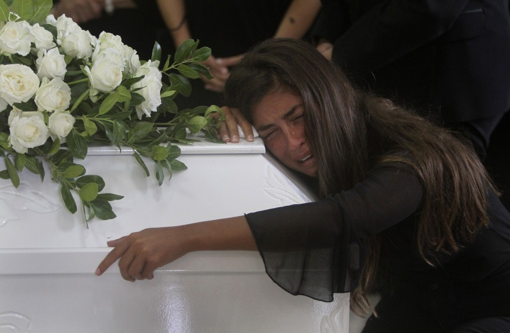 The sister of Nicole al-Helou, who was killed by the explosion Tuesday that hit the seaport of Beirut, mourns on her coffin during her funeral, in Sar...