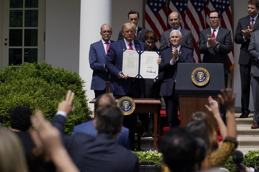 FILE - In this June 5, 2020 file photo, President Donald Trump poses for a photo after signing the Paycheck Protection Program Flexibility Act during ...