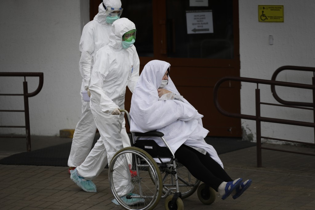 In this photo taken on Tuesday, April 14, 2020, Belarusian healthcare workers wearing face masks and costumes to protect from coronavirus carry a pati...