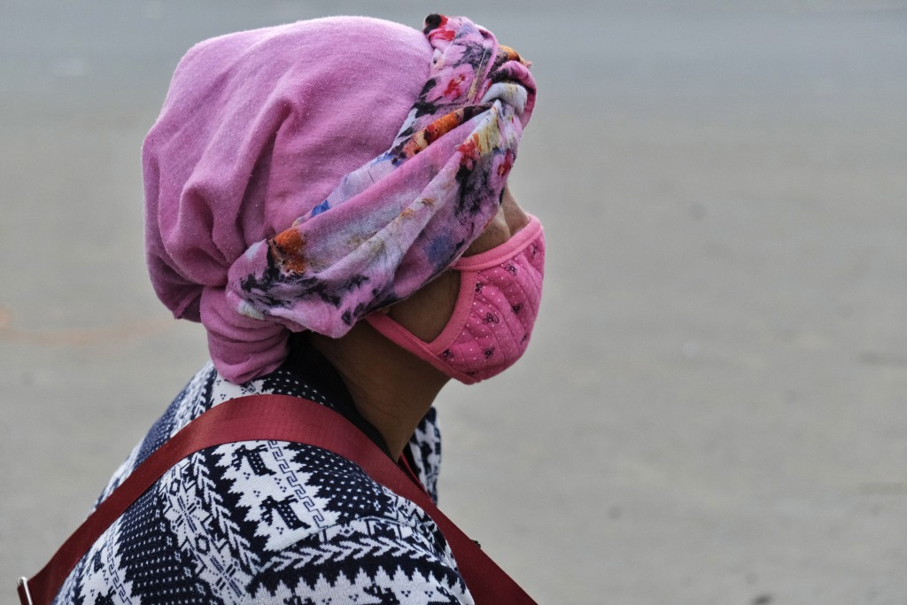 A Naga woman wears a face mask and sits by the side of a road selling poultry in Kohima, capital of the northeastern Indian state of Nagaland, Saturda...
