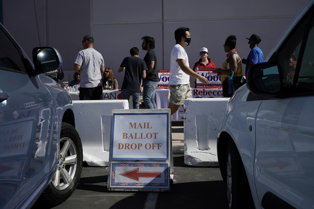 People wait in line at one of a few in person voting places during a nearly all-mail primary election Tuesday, June 9, 2020, in Las Vegas. (AP Photo/J...