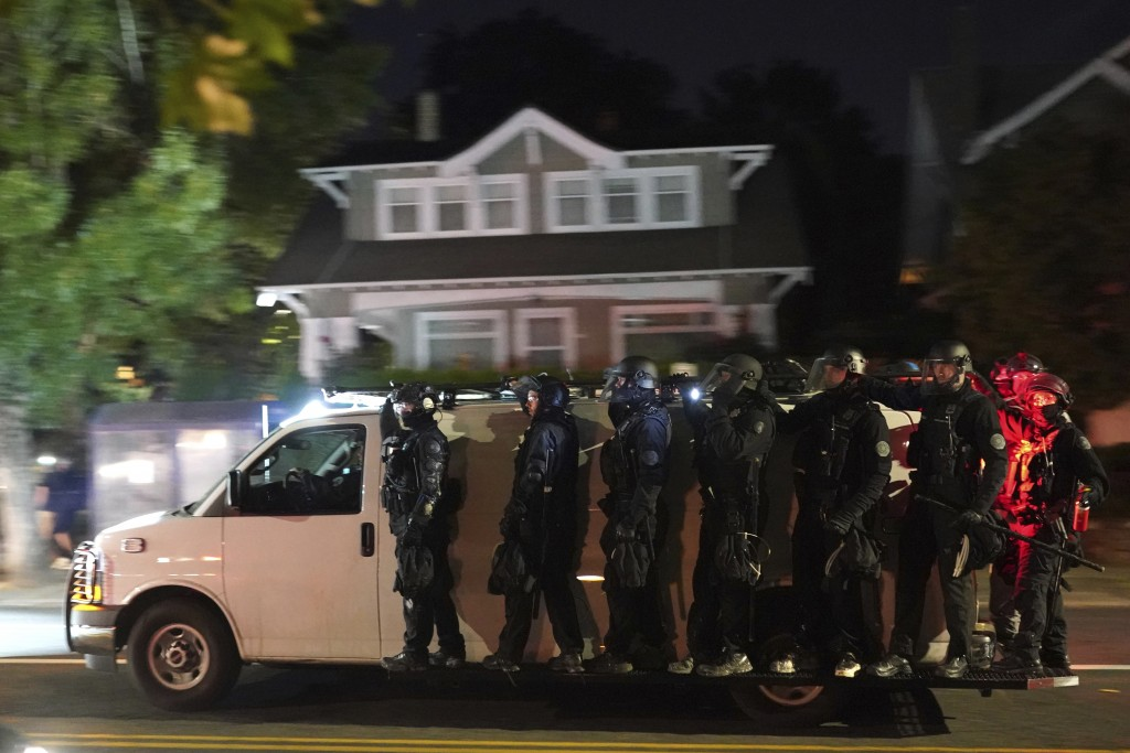 Portland police hang off the side of a riot van while searching for protesters in the Laurelhurst neighborhood after dispersing a crowd of about 200 p...